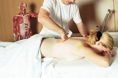Physical therapist is a High Paying Medical Jobs Without Medical School. Man using physical therapy techniques on woman in occupational health room