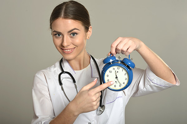 Physical therapist pointing at a clock indicating a physical therapist working hours