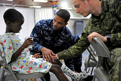 21 Reasons to Be a Physical Therapist - Military Therapists assessing a patient's injured leg.